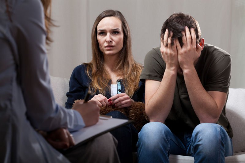 Young unhappy couple at odds on therapy visit